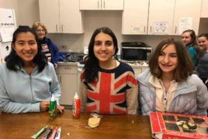 Teenage girls decorating cookies