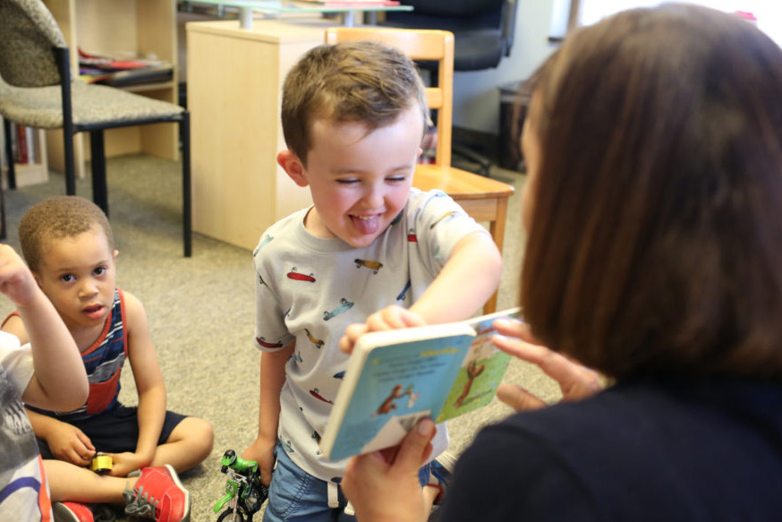 boy pointing at book smiling