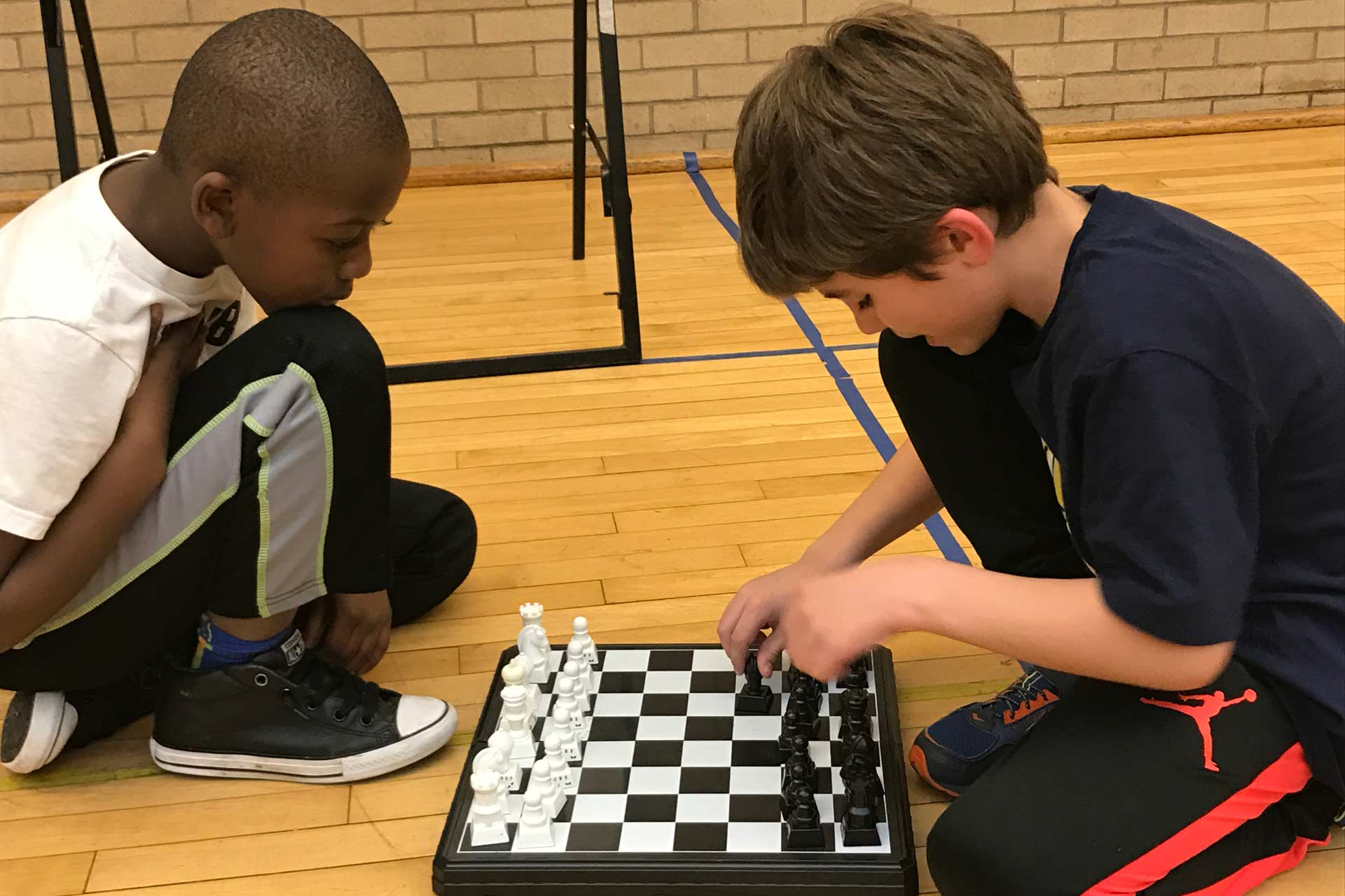 two boys playing a game of chess together