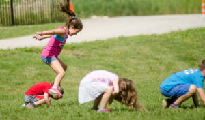 Kids playing leap frog outside