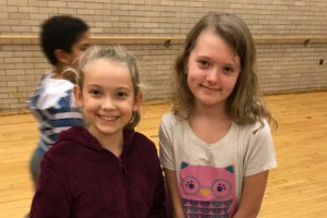 Two friends smiling together in gym